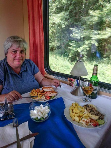 Corinne eating dinner in the dining car while enjoying train travel in Eastern Europe.