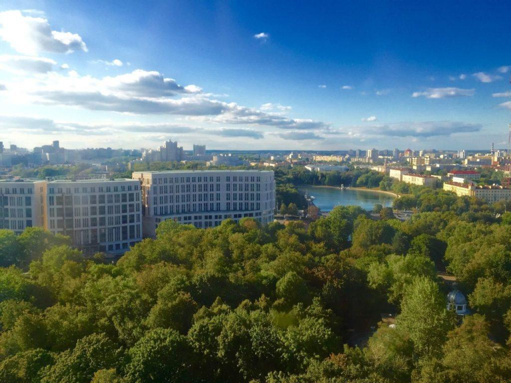 Minsk cityscape view with leafy trees, sparkling lake, and the buildings of the city.