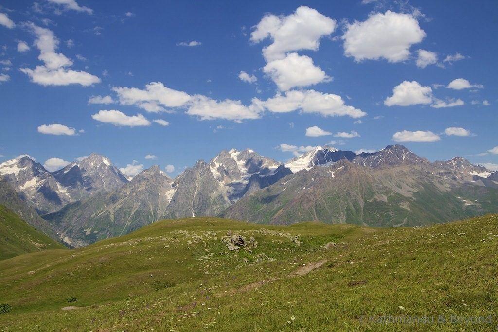 Jagged mountains behind an alpine meadow in Georgia.