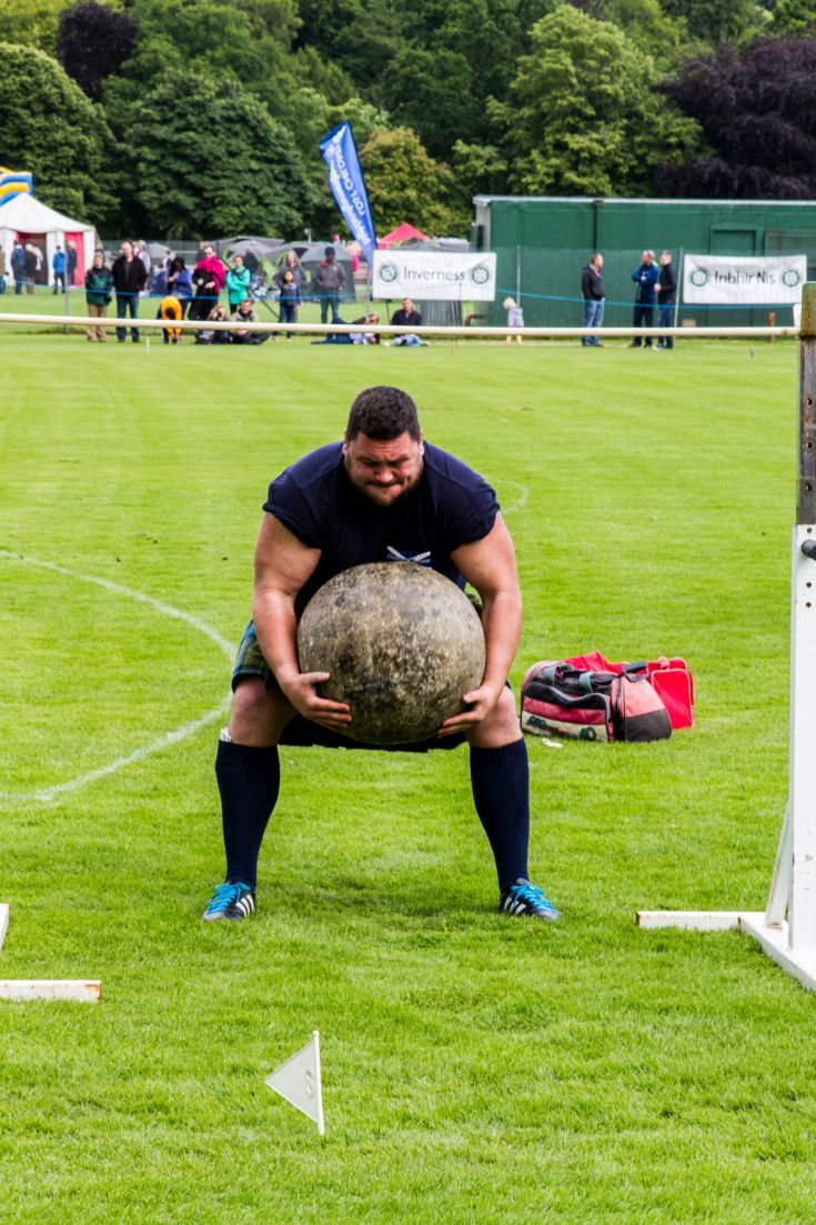 Man lifting a huge stone, unique to the Inverness Highland Games