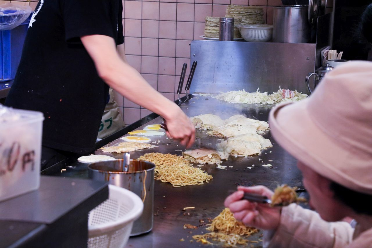 Frying the okonomiyaki and one person eating it