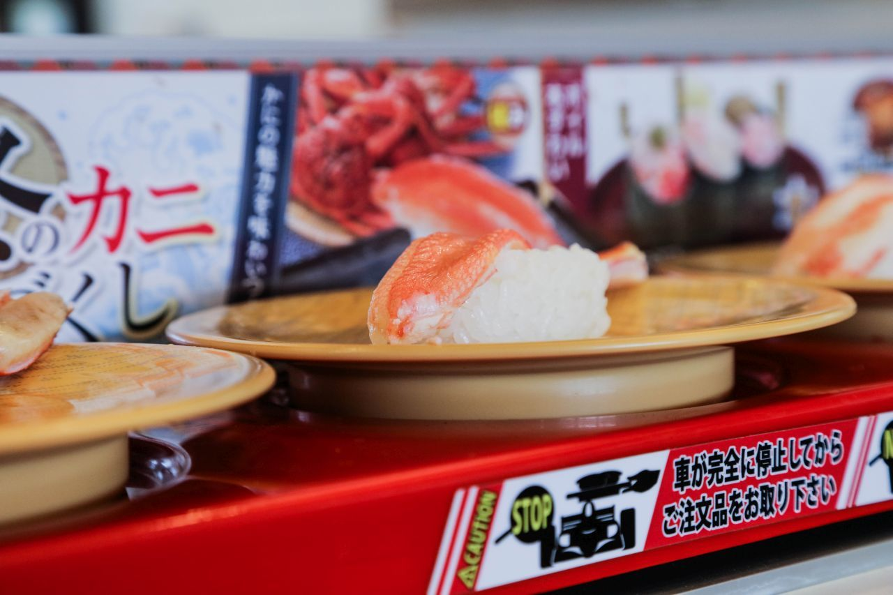 Crab sushi being delivered on a sushi train to the table. A popular Japanese dish to add to your Japan food guide.
