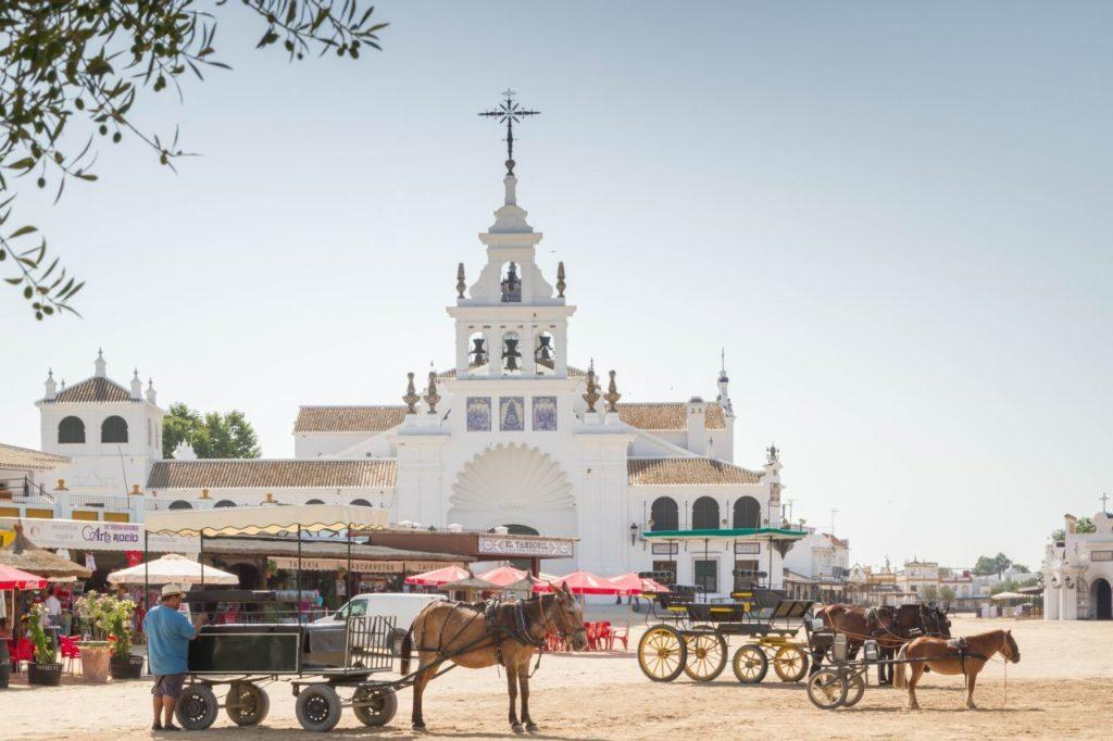 Horse carts and wagons are waiting for passengers outside the cathedral in El Rocio.