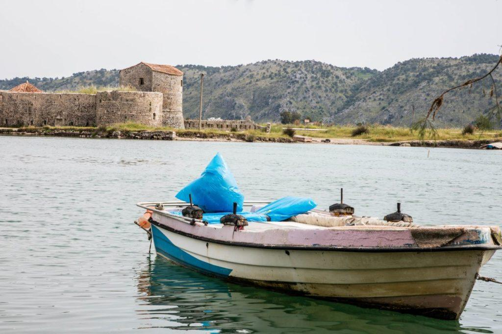 A fishing boat with Butrint in the background.