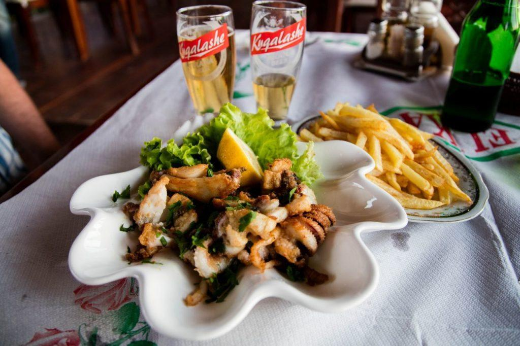 Having a lunch of calamari right on the seaside.