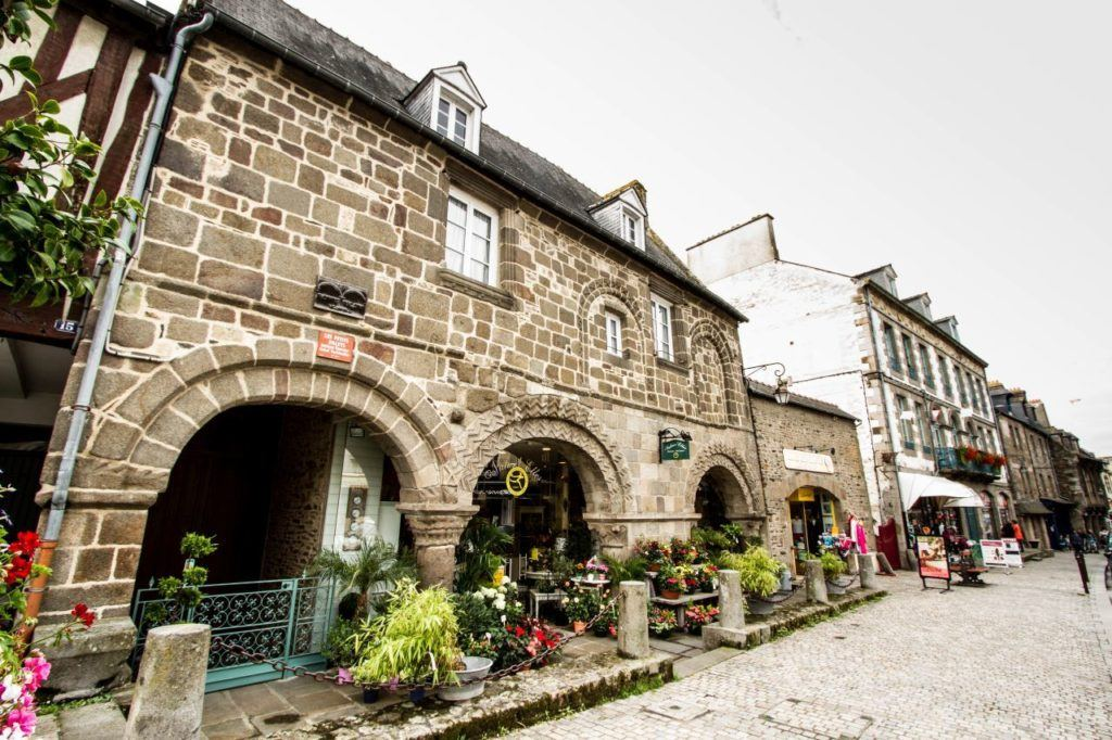 Old stone house on cobblestone pedestrian street in Brittany, France.