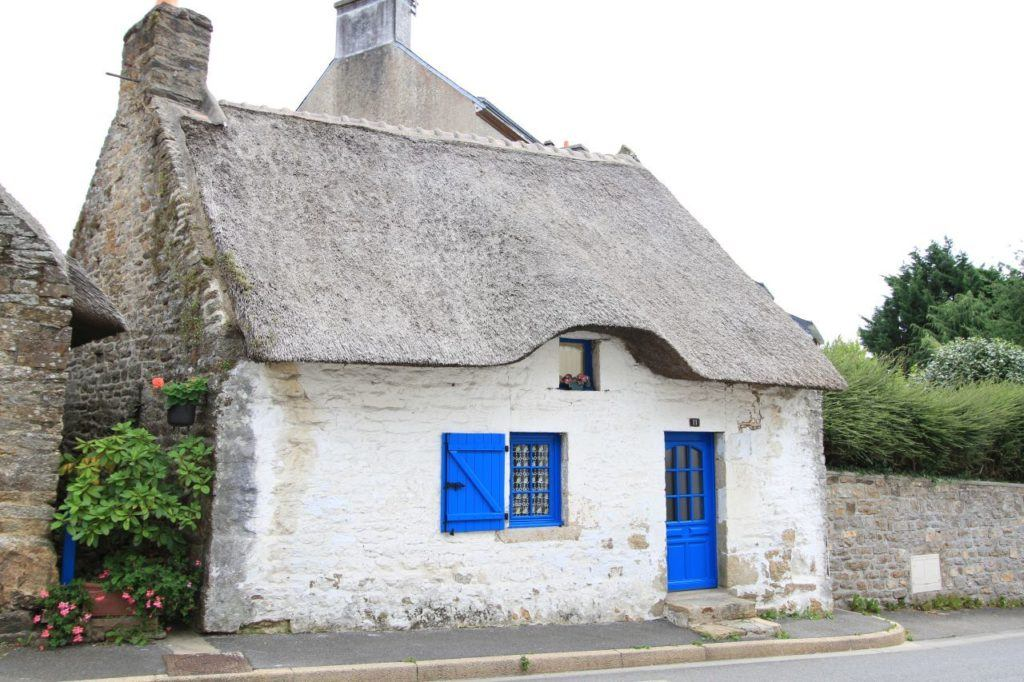 Adorable white-washed stone cottage with thatched roof and bright blue doors adds to the charm of another quaint French village.