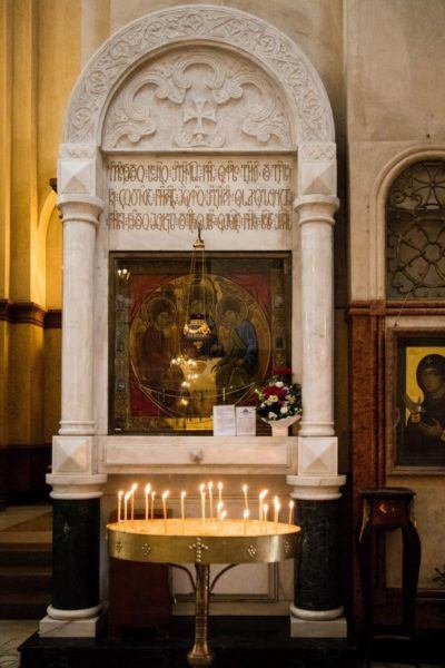 Tbilisi church interior showing icons and candle votives.