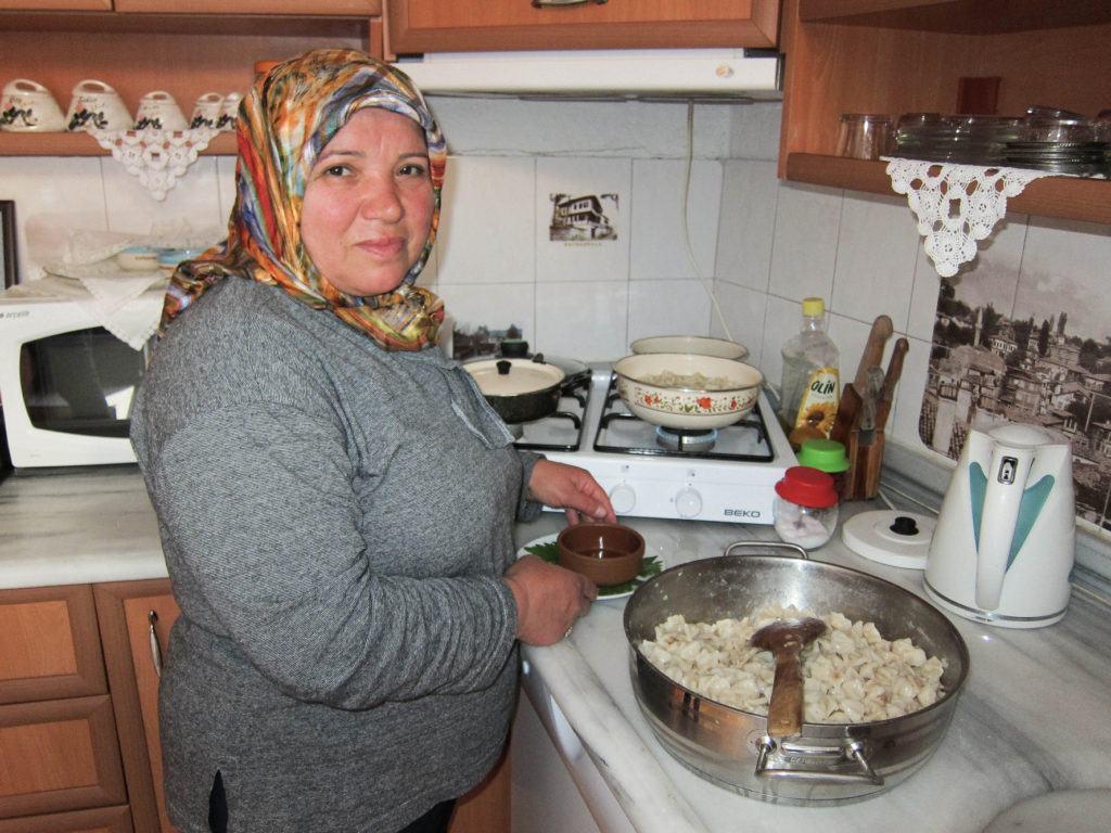 Woman preparing manti, Turkish dumplings.