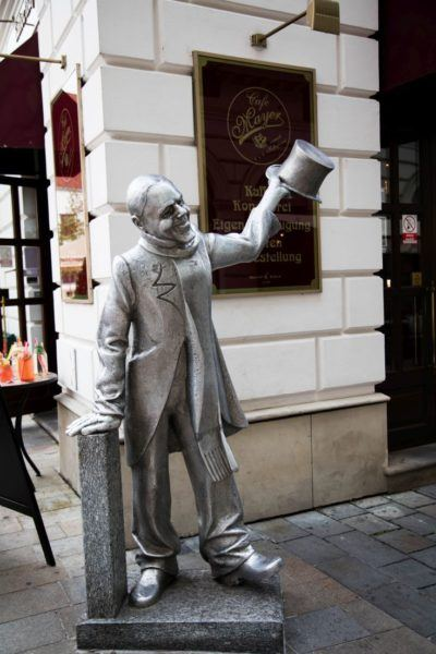 Smiling man sculpture welcomes visitors to old town Bratislava.