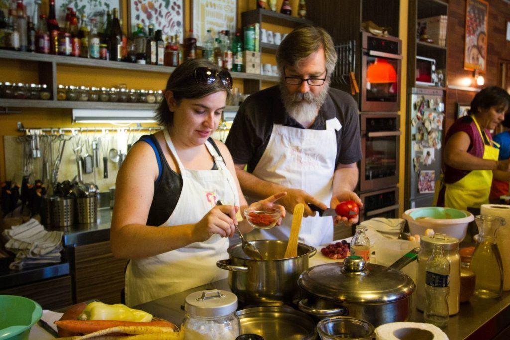 Devon adds plenty of paprika to the paprikash while Jim cuts a tomato.