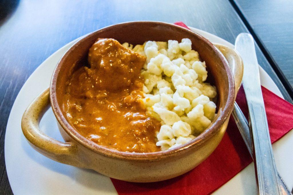 Chicken paprikash with spaetzle served up in a crock-ware bowl.
