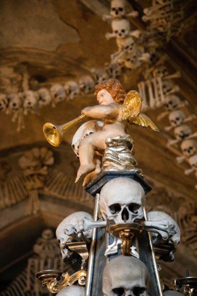 Cherub angel with horn atop skull pillar.