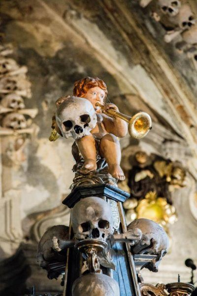 Closeup of angel playing horn and holding a human skull.