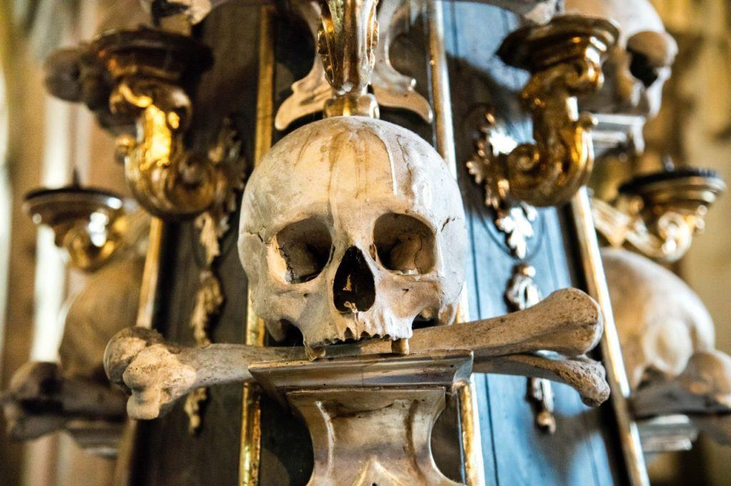 Human Skull with bone in mouth make up part of the decorations in Sedlec Bone Church in Kutna Hora, Czechia.