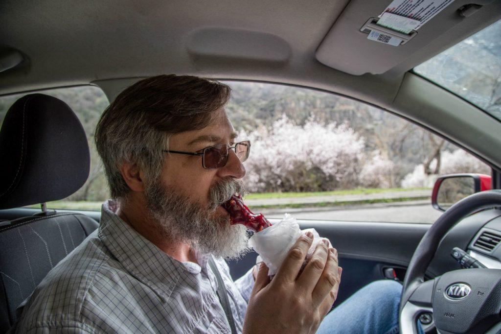 Jim takes a bite of churchkhela for the road.