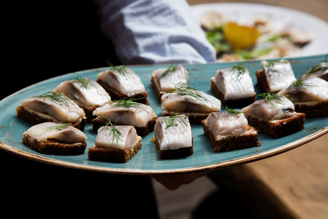 Pieces of fresh herring with dill atop rye bread.