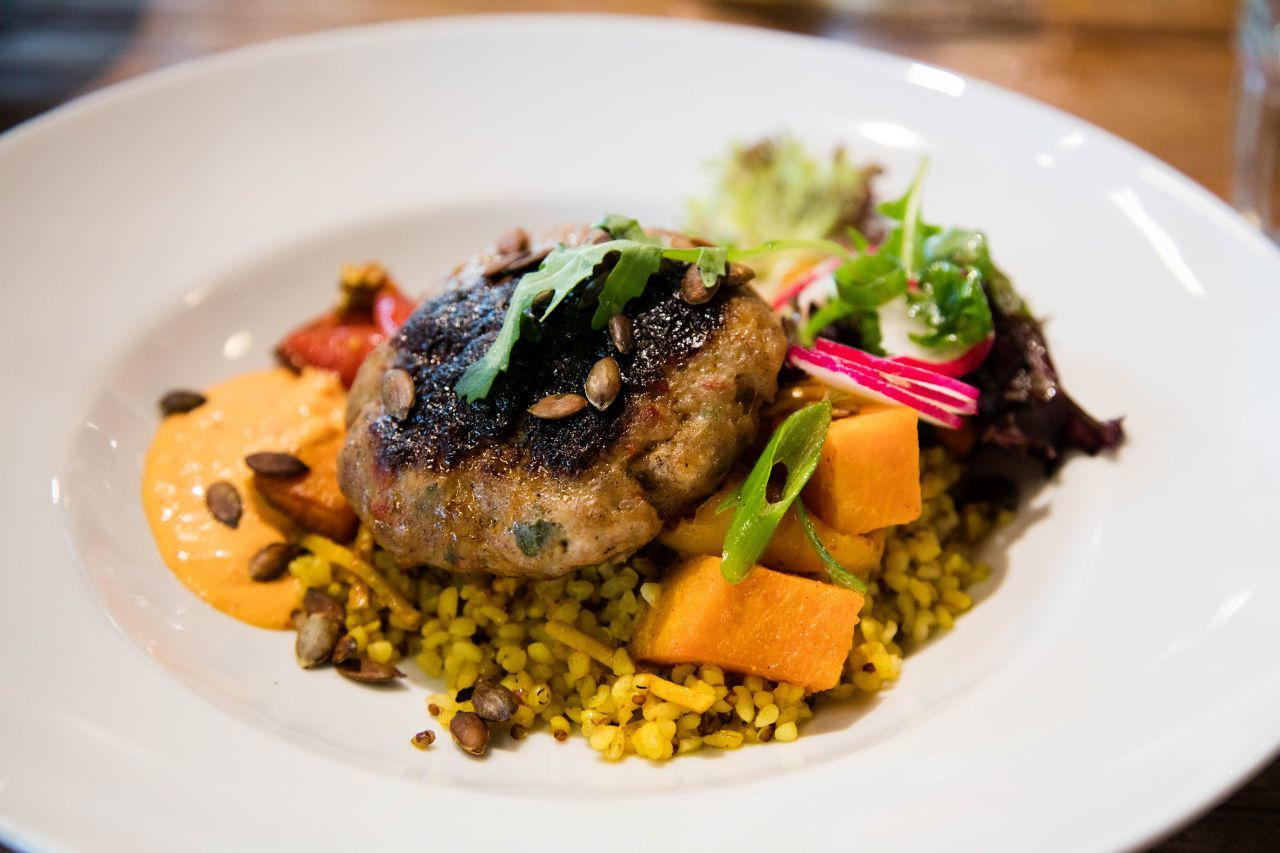 Turkey burger served with bulgar and sweet potato and root vegetable medley with fresh greens.