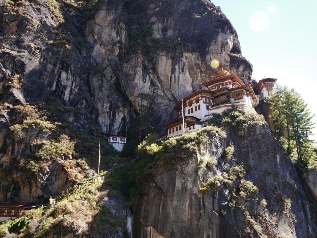 White washed temple with painted roofs and pagoda on a cliff in Bhutan.