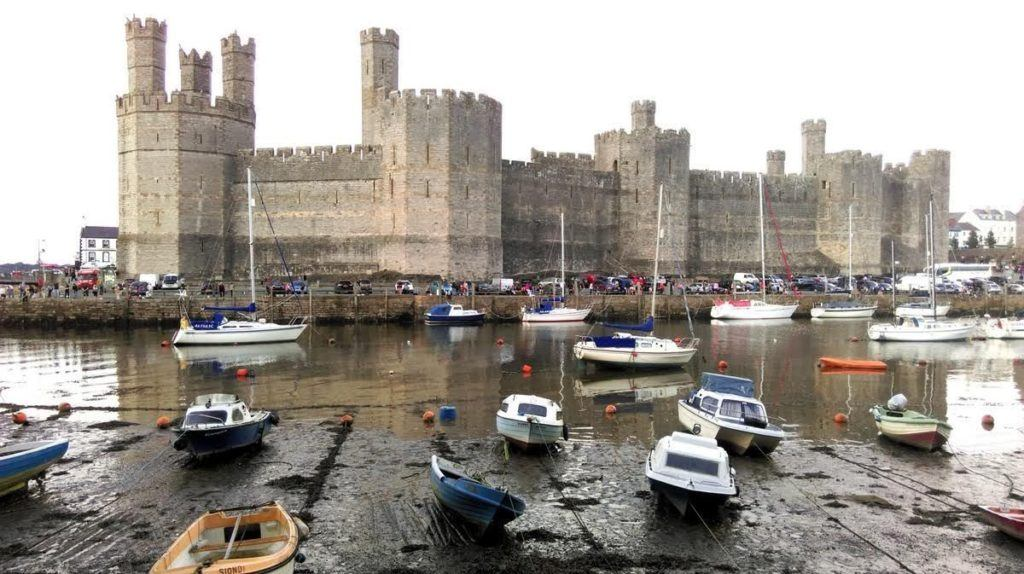 Small boats pulled up on the rocks in front of Caernarfon Castle in Wales.