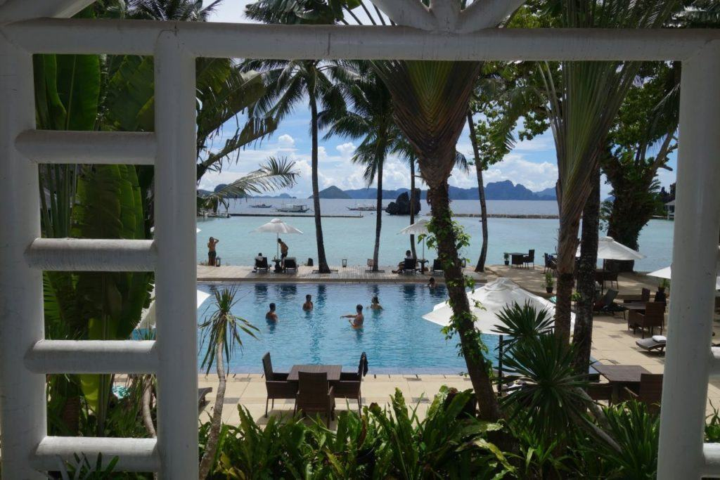 Tropical resort El Nido in Palawan, Philippines with a swimming pool, palm trees, beach front and fishing boats.