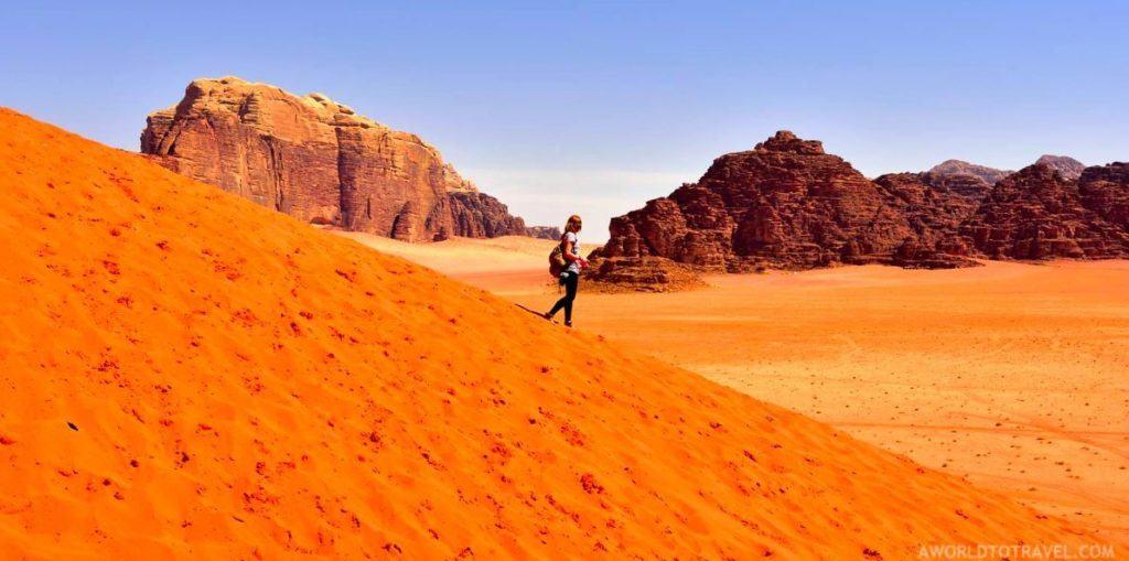 Woman walks down the slope of an orange sand dune in Wadi Rum.