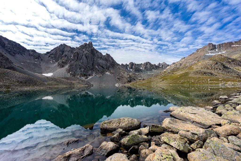 Crystal clear mountain lake under a blue sky in Jyrgalan, Kyrgyzstan.
