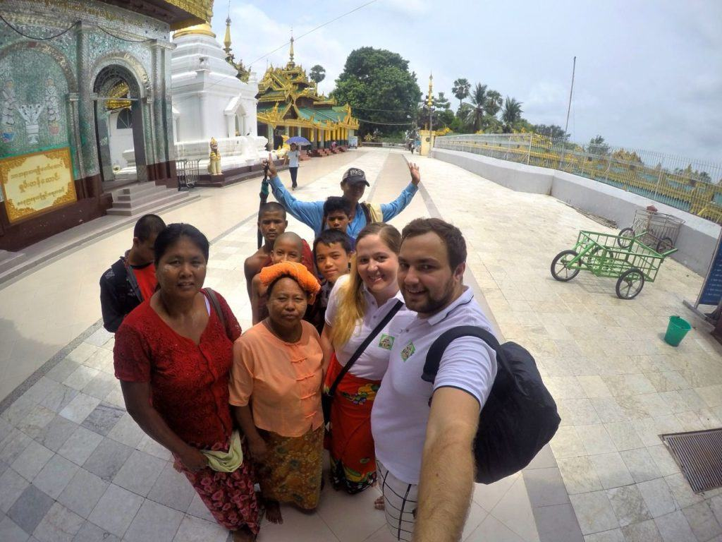 A group of visitors pose for the camera in a Myanmar temple.