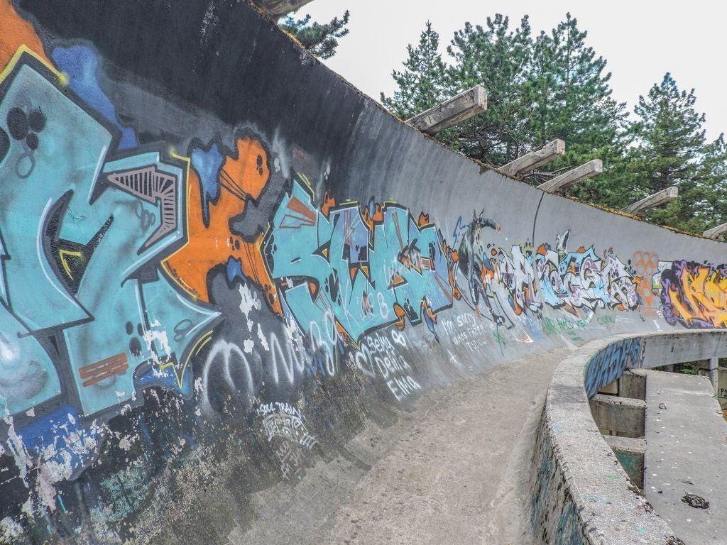 Abandoned bobsled track in Sarajevo covered in graffiti.