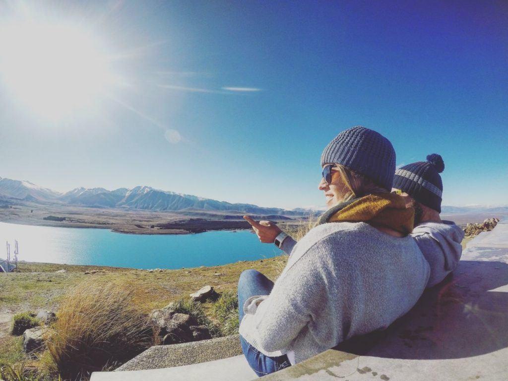 Two travelers enjoy the view of Lake Tekapo in New Zealand.