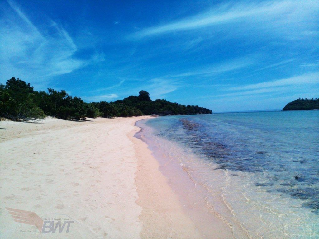 White sandy beach and crystal blue water in the Carmoan Peninsula, Phillipines.
