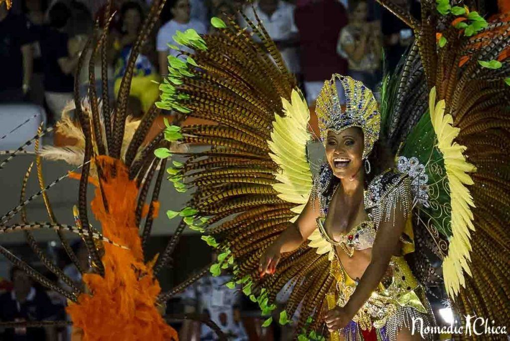 Woman dressed in traditional Brazilian carnival dancer costume with yellow and green flowers.