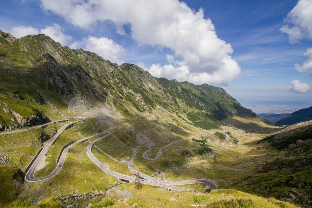 Transfagarasan Highway in Romania winds down the mountain valley with multiple hairpin curves.