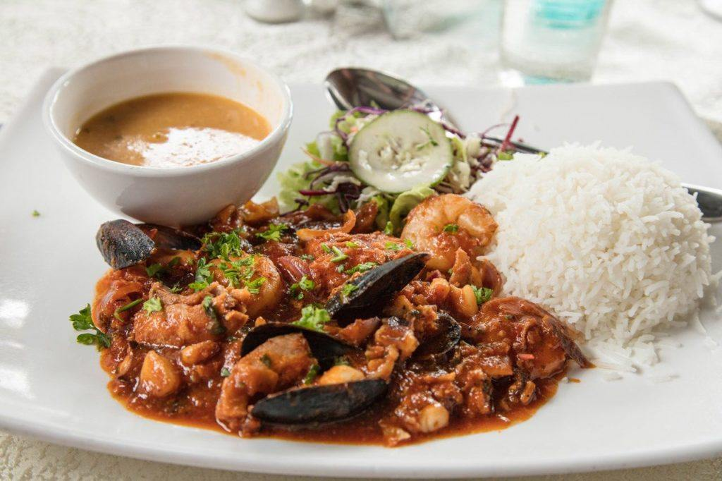 Seafood curry plate with rice and sauce.