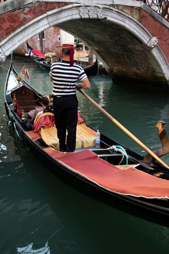 A traditional Venetian gondola goes under a bridge.