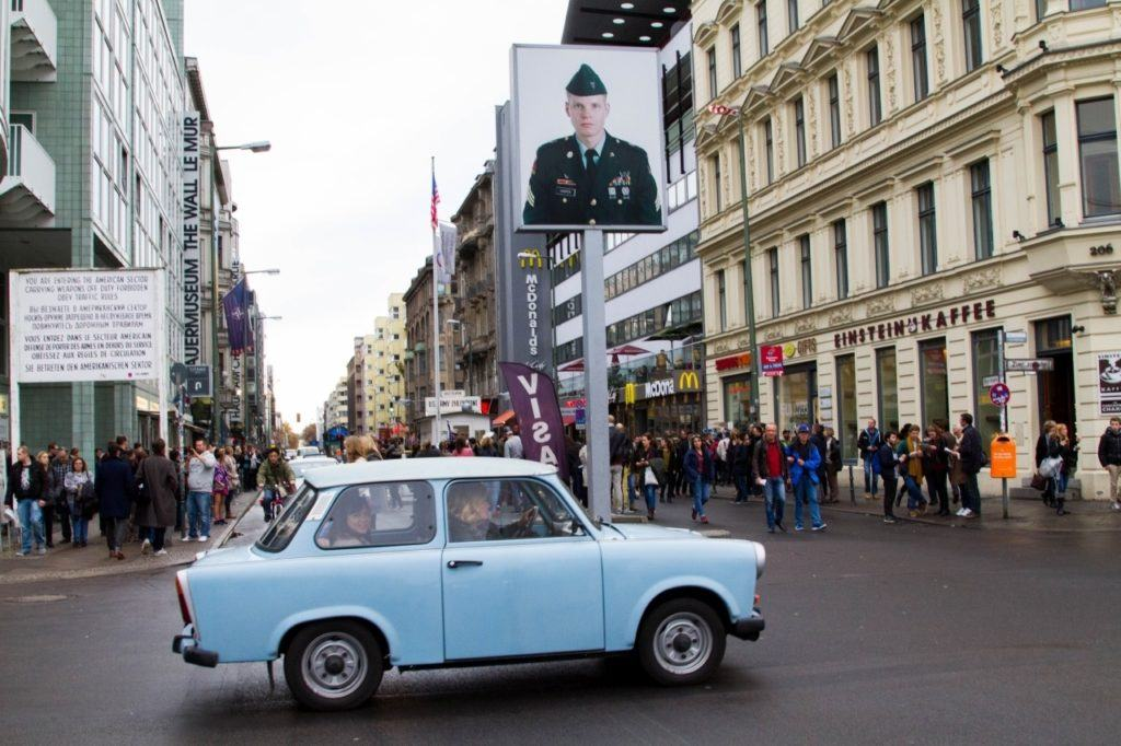 A trabi drives in front of Checkpoint Charlie Berlin Germany - one of the first things anyone should do when visiting Berlin.
