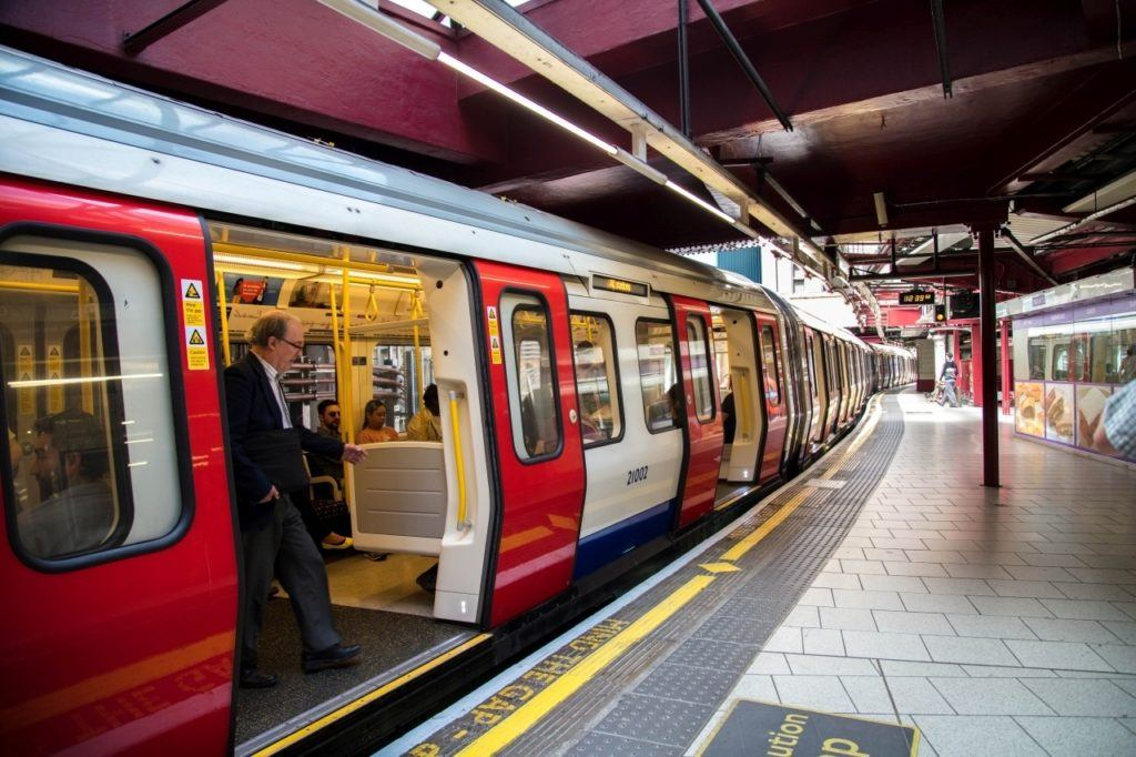 London tube train opens doors at station.