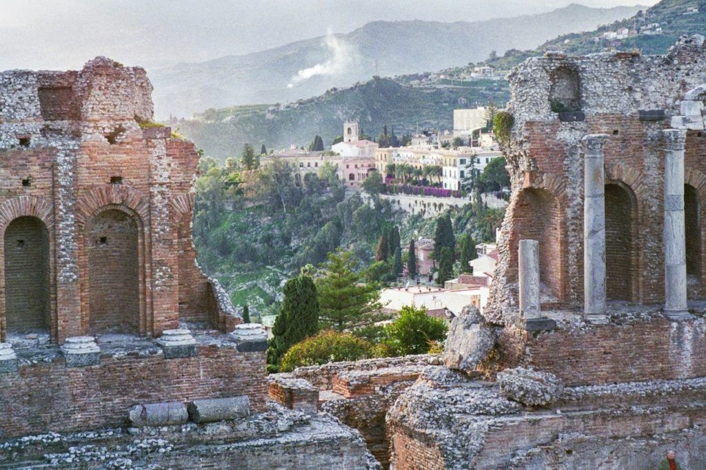 A view of the city seen through the ruins of the ancient Roman Amphitheater of Taormina.