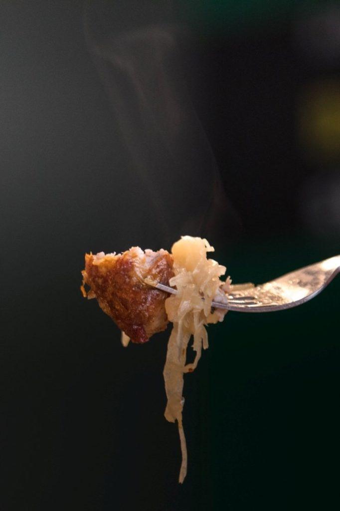 One bite of bratwurst with sauerkraut.