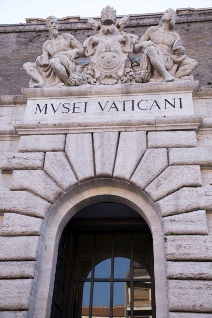 Door and Entry to Vatican City Museum with Latin inscription and a decorated mantel.