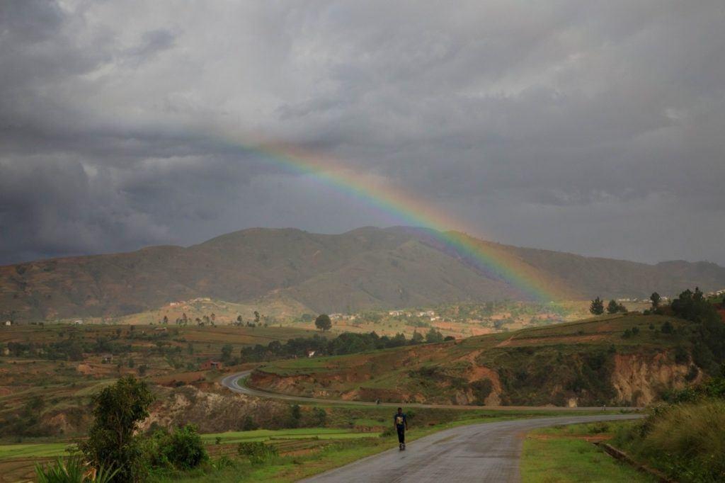 A man walks down a road in Madagascar under a rainbow.