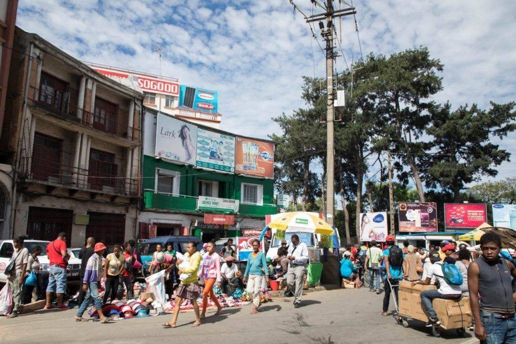 Antananarivo city scene with lots of people walking and things for sale on the sidewalk.