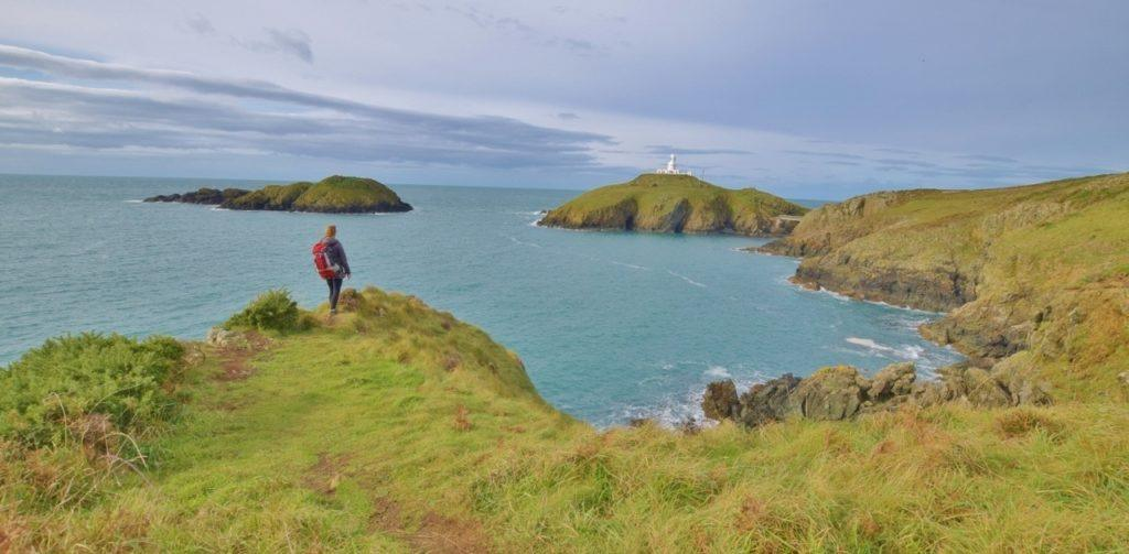 One hiker looks over the coast and at the water.