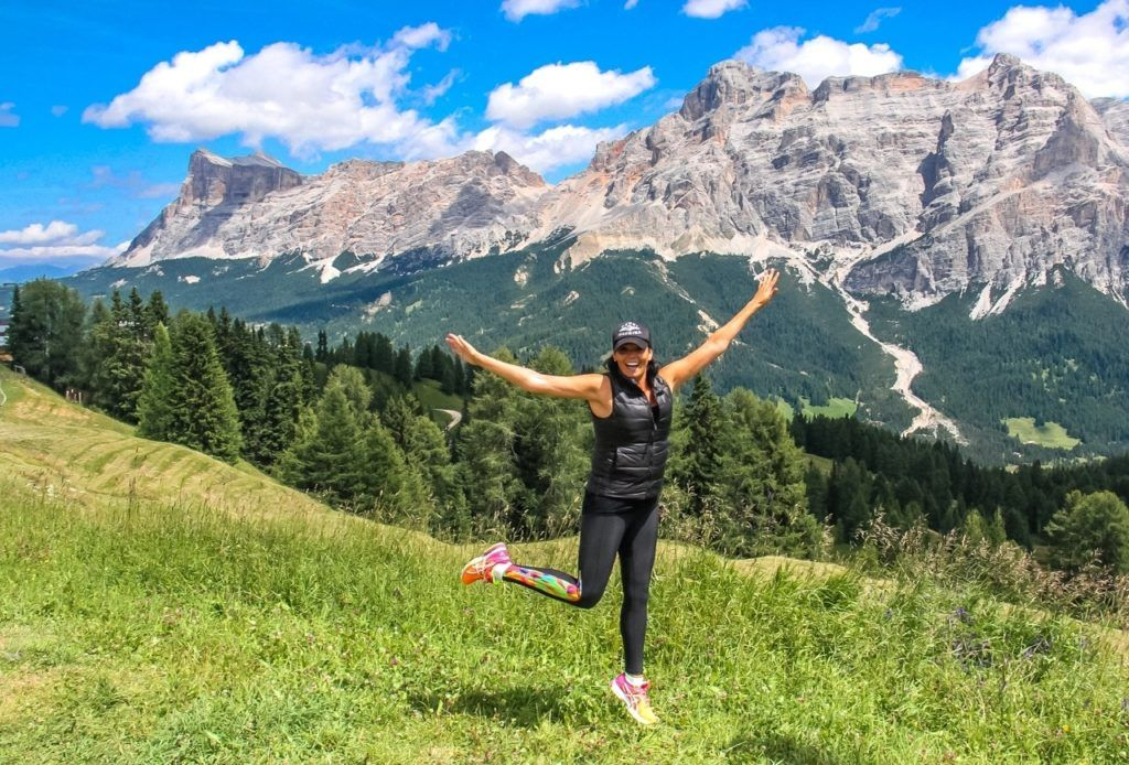 Girl smiling and kicking foot up in Italy's Dolomite mountains.