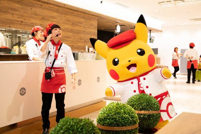 Pikachu and helper at the Pokemon Cafe.