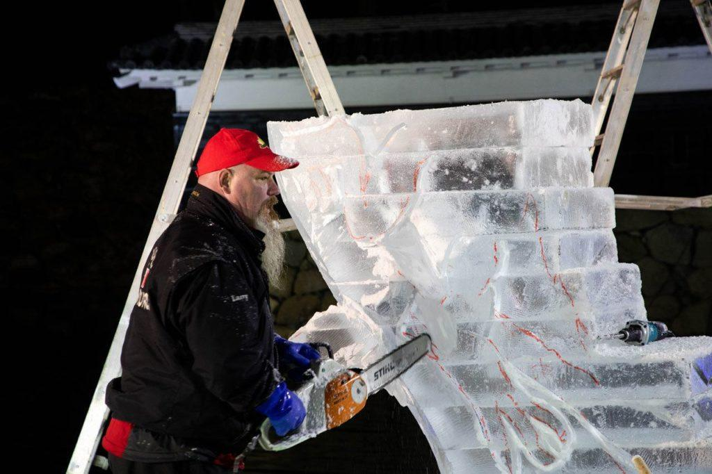 Canadian ice sculpture artist making some of the first cuts after the design is sketched on the ice block.