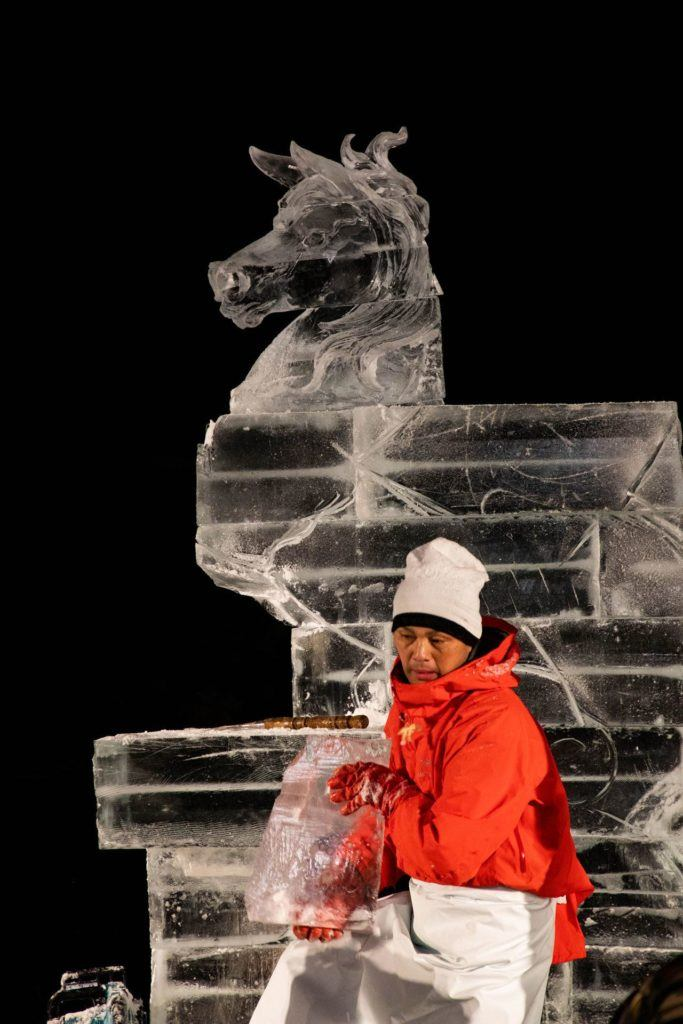 Artist taking off big chunks of ice before carving horse.