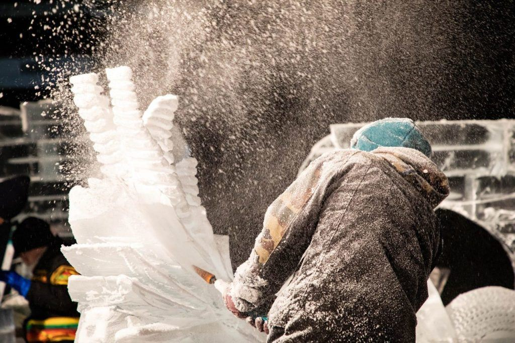 Ice shards fly in a cloud as the artist chainsaws away.