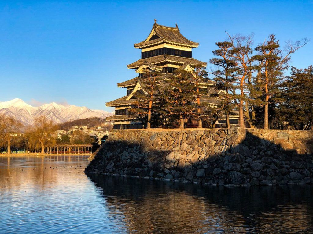Matsumoto Castle with snow on Japanese Alps in background, a fantastic Japan winter destination.