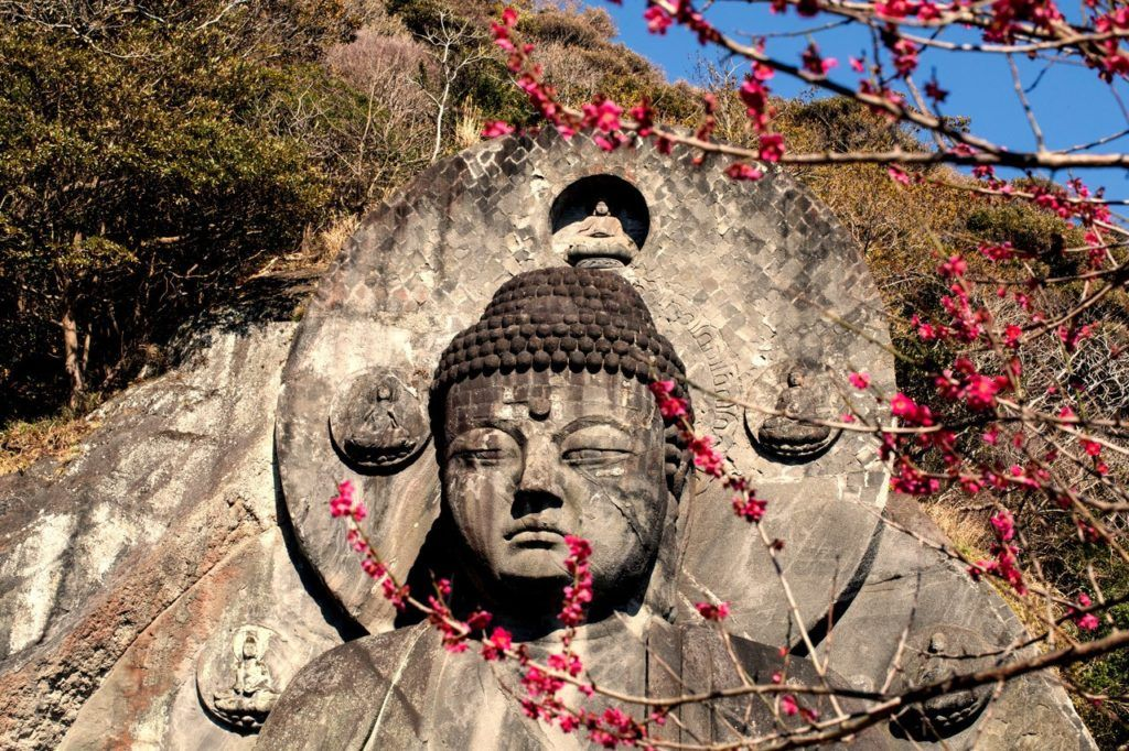 Large Buddha carving with tree blossoms high atop Mount Nokogiri.
